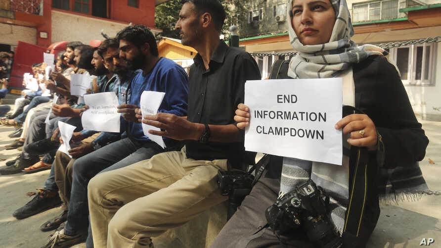 FILE - Kashmiri journalists display placards during a protest against the communication blackout in Srinagar, Indian controlled Kashmir, Oct. 3, 2019.