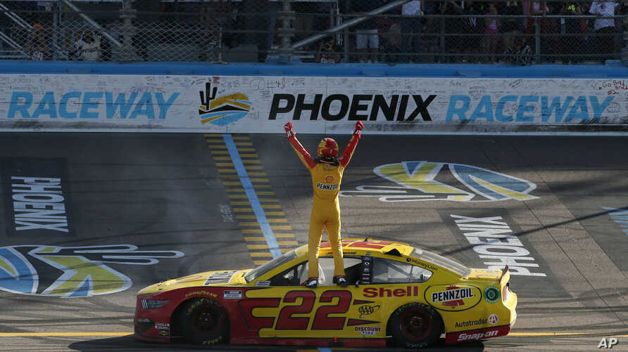 Driver Joey Logano stands on his race car at the start-finish line as he celebrates after winning the NASCAR Cup Series auto…