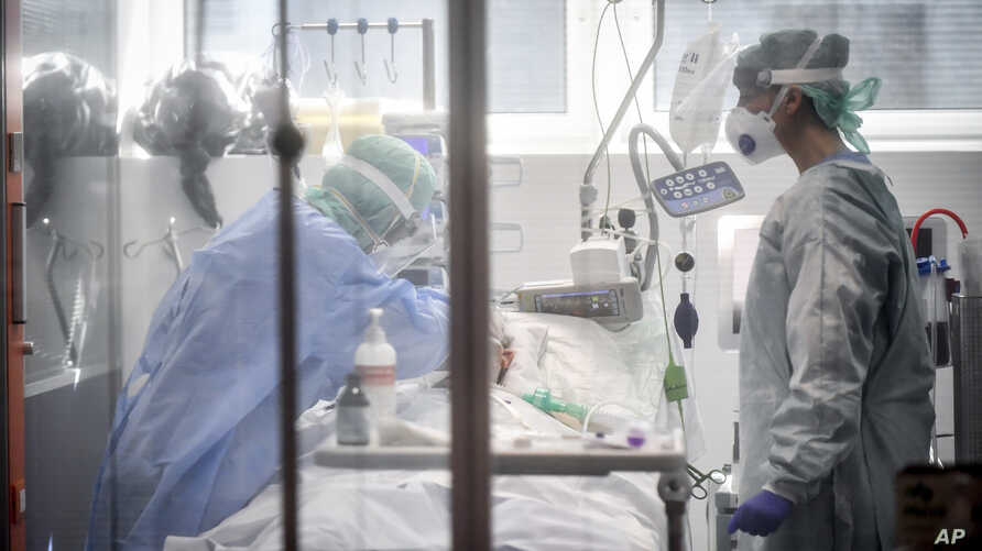 FILE - Medical personnel work in the intensive care unit of a hospital in Brescia, Italy
