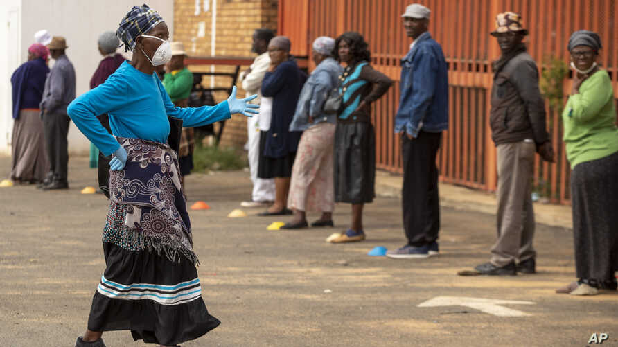 A worker wearing a face mask and gloves to protect herself against coronavirus, joins the queue to receive her social grant outside a pay point in Thokoza, east of Johannesburg, South Africa, March 30, 2020.
