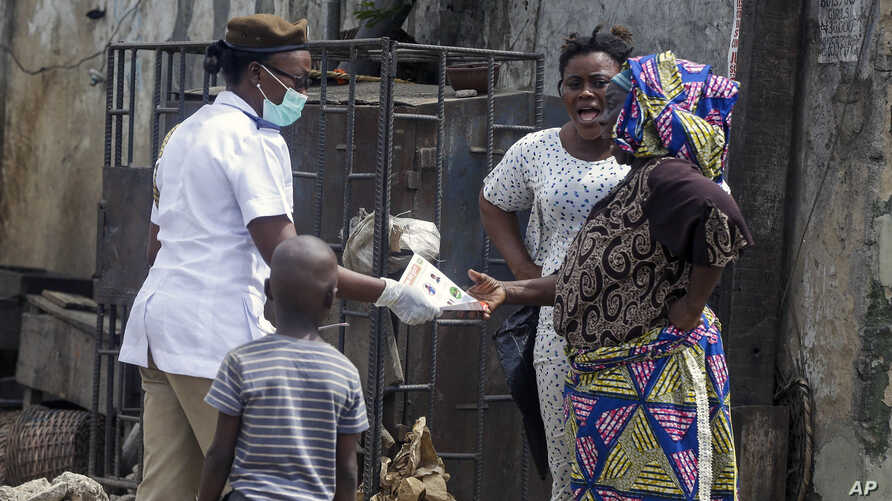A health worker, center, distributes leaflets on how people should protect themselves from the new coronavirus, in Lagos, Nigeria, March 31, 2020.