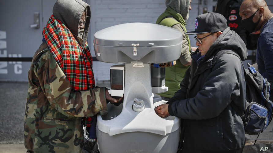 Visitors waiting to collect free food outside the Bowery Mission are instructed to wash their hands at a kiosk due to coronavirus concerns, April 1, 2020, in New York.