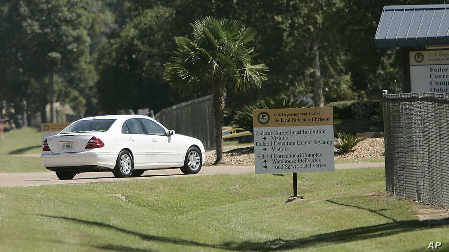 FILE - In this Sept. 26, 2006, file photo a person drive through the gates of a federal prison in Oakdale, La. The federal…