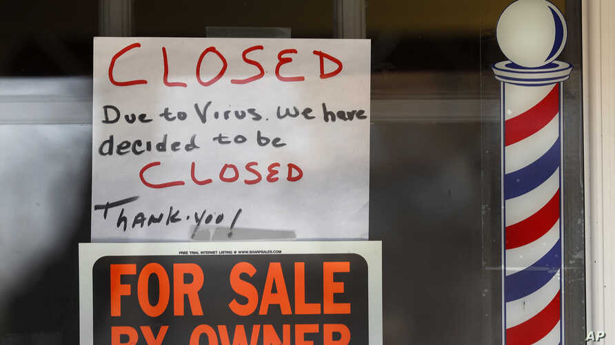 """For Sale By Owner"" and ""Closed Due to Virus"" signs are displayed in the window of Images On Mack in Grosse Pointe Woods, Mich., April 2, 2020."