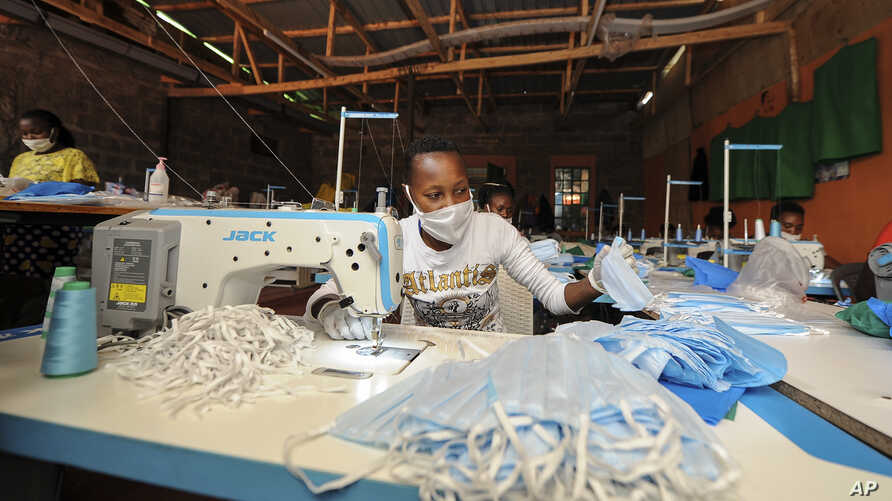 A worker sews surgical-type face masks to be used to curb transmission of the new coronavirus, at the New Dawn company