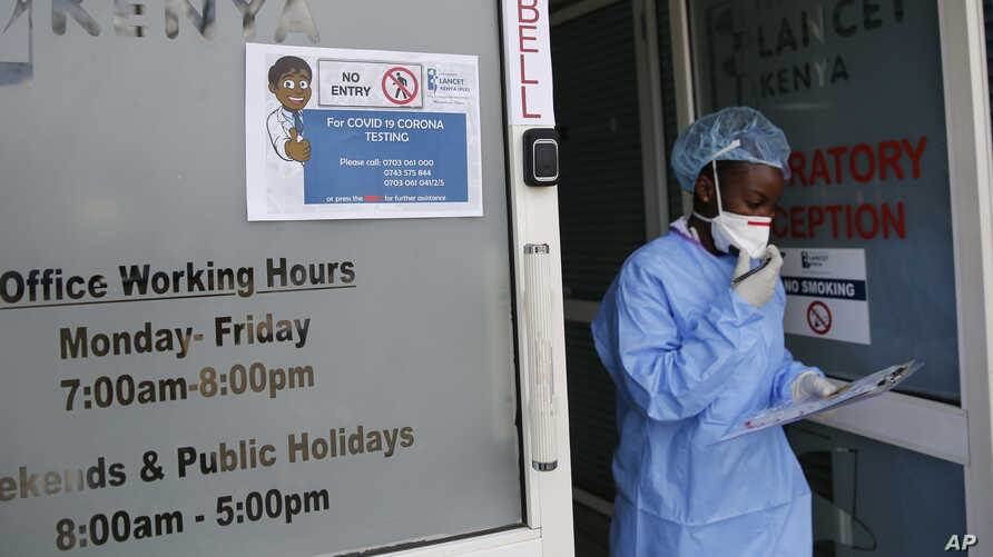 FILE - Laboratory technician Irene Ooko walks outside to take a nasal sample from a patient