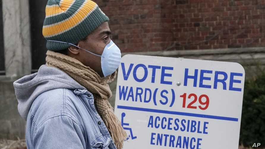 Voters masked against coronavirus line up at Riverside High School for Wisconsin's primary election,  April 7, 2020, in Milwaukee.