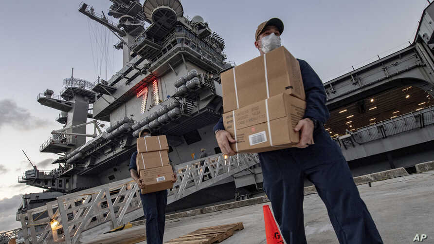 Sailors assigned to the aircraft carrier USS Theodore Roosevelt move ready to eat meals for sailors who have tested negative for COVID-19 and are being taken to local hotels in an effort to implement social distancing at Naval Base Guam,April 7, 2020.