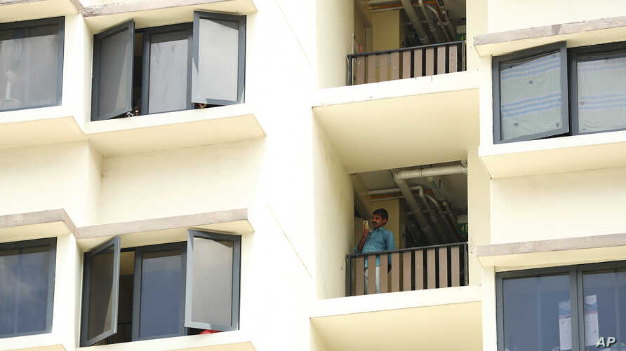 A foreign worker talks on the phone outside his room at the WestLite Toh Guan dormitory after it was declared an isolation area.