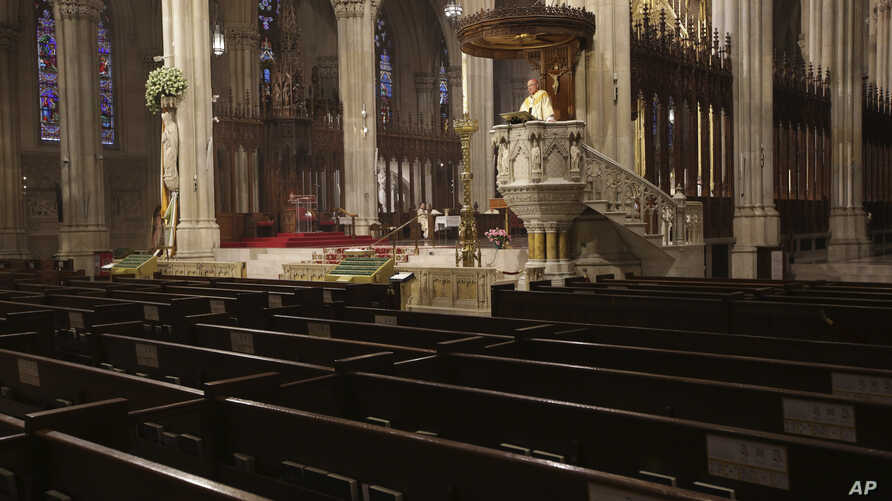 Archbishop Timothy Dolan delivers his homily over empty pews as he leads an Easter Mass at St. Patrick's Cathedral in New York, Sunday, April 12, 2020.