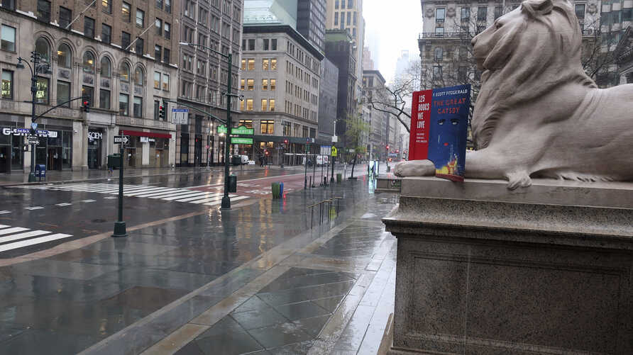 Fifth Avenue in front of the New York Public Library is empty on a rainy day in New York, Monday, April 13, 2020. Gov. Andrew…