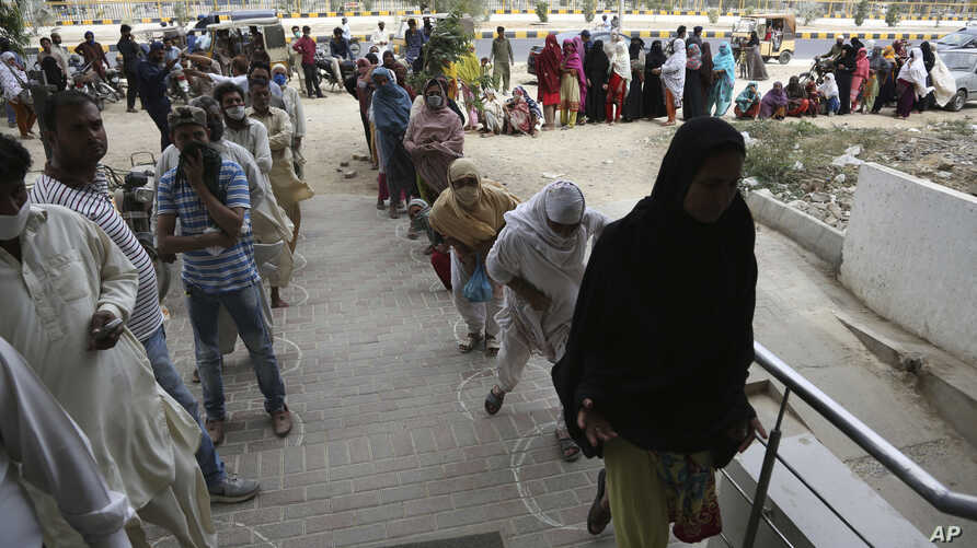 People wait to receive cash under the government's Ehsaas Emergency Cash Program for families in need, during a government-imposed nationwide lockdown to help contain the spread of the coronavirus, in Karachi, Pakistan, Tuesday, April 14, 2020.