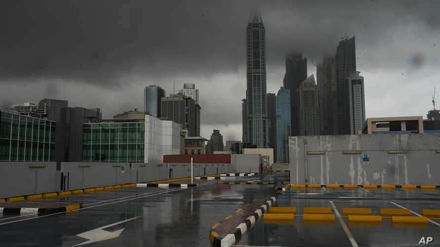 Storm clouds cover up the tops of buildings in the Dubai Marina as rain falls on a parking lot that stands empty over the coronavirus pandemic in Dubai, United Arab Emirates, April 15, 2020.