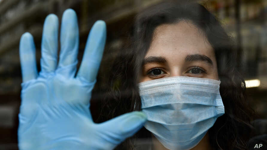 In this Thursday, April 16, 2020 photo, chemist Amaya Pascual poses for a photograph in her pharmacy in Pamplona