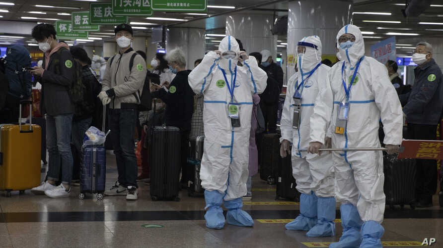 Workers in protective clothing process passengers from Wuhan after they arrive on a high speed train in Beijing on Sunday,…