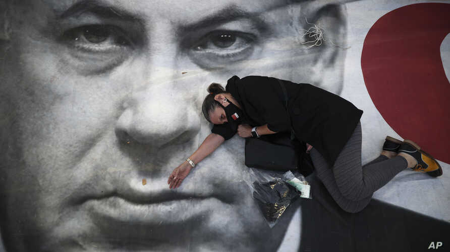 A woman takes part in a protest against Israeli Prime Minister Benjamin Netanyahu, seen on the poster, in Tel Aviv, Israel, April 19, 2020.