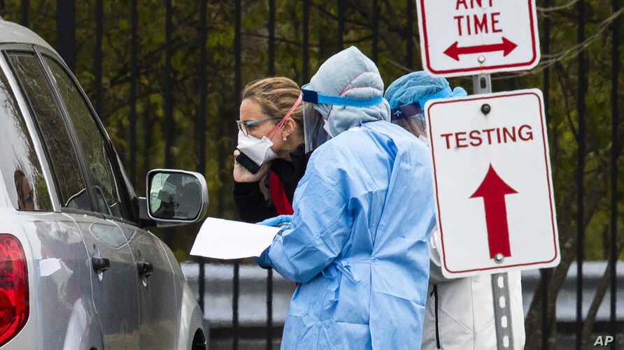 Medical personnel from Montgomery County, Md., check patients arriving for a COVID-19 drive-in testing in Silver Spring.
