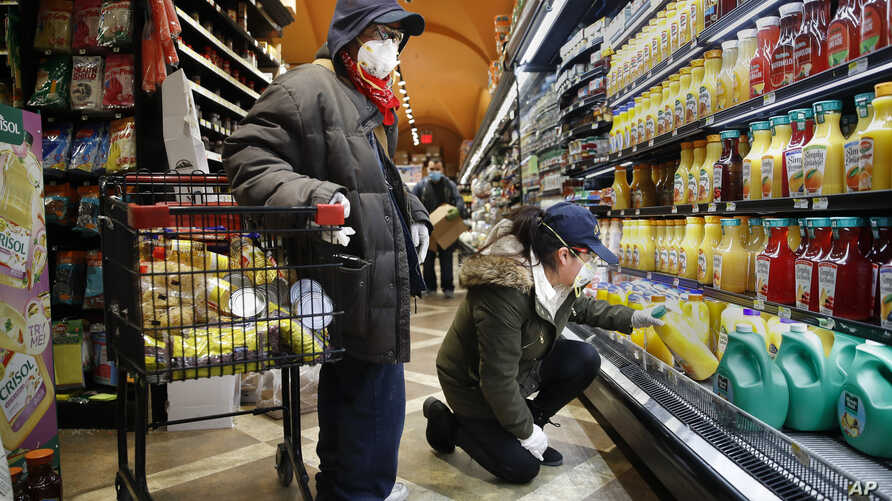 Francisco Ramírez, left, and Sandra Perez, right, shop at a grocery store for goods they intend to donate to needy families, Saturday, April 18, 2020, in the Harlem neighborhood of New York.