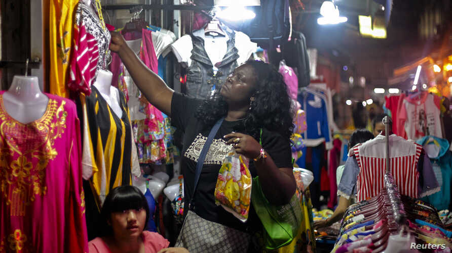 "FILE - An African woman shops at a market at ""African village"" in Guangzhou, Guangdong province, October 25, 2014."