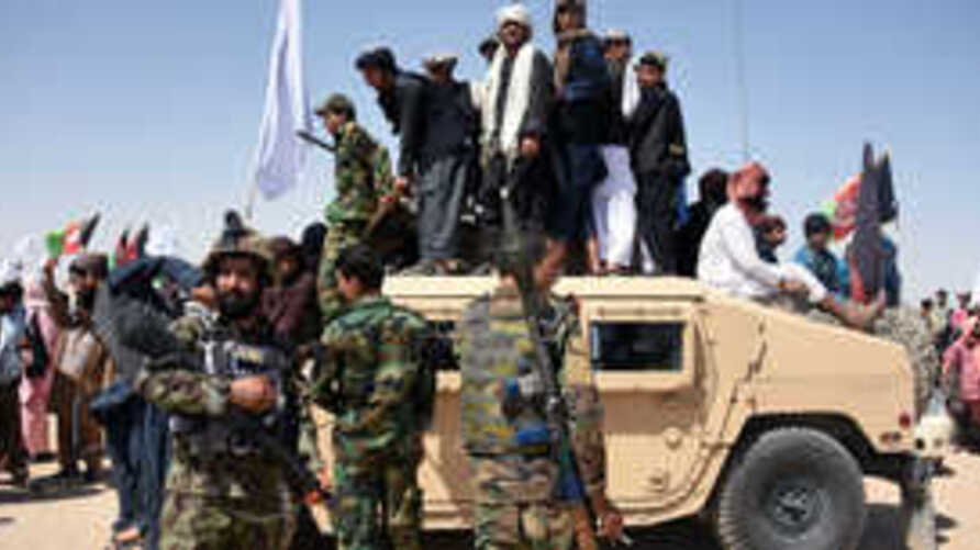 In this photo taken on June 17, 2018, Afghan Taliban militants and residents stand on a armoured Humvee vehicle of the Afghan…