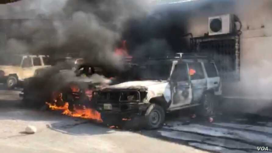 Cars burn after angry police protesters set fire to them at the Ministry of Finance. (VOA Creole/Matiado Vilme)