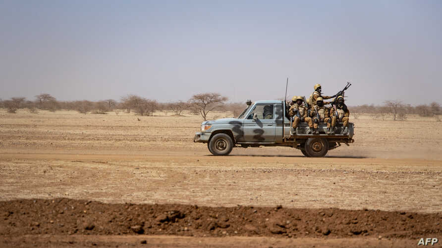 FILE - Burkina Faso soldiers patrol atop a pick-up truck on the road between Dori and Goudebo, in Burkina Faso, Feb. 3, 2020.