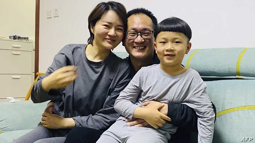 This handout photo taken on April 27, 2020 and released by Wang Qiaoling, shows human rights lawyer Wang Quanzhang (C) embracing his wife Li Wenzu and their son after they were reunited in Beijing, China.