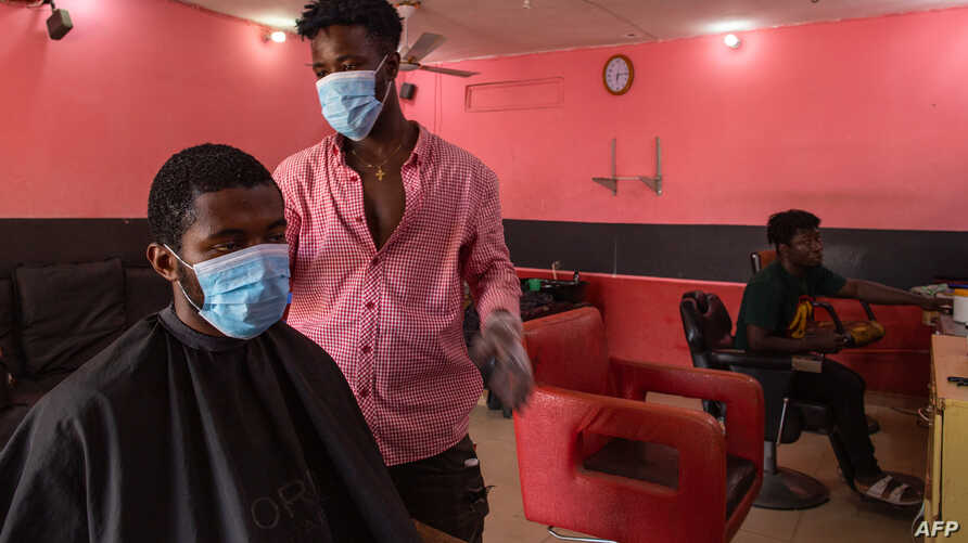 Kofi, a barber, resumes work after the partial lockdown halt the spread of the COVID-19 was lifted in Accra, Ghana, April 20, 2020.