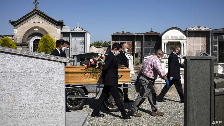Workers of a funeral home company pull the coffin of a COVID-19 victim for burial at the cemetery near Cuneo, northwestern Italy, April 24, 2020.