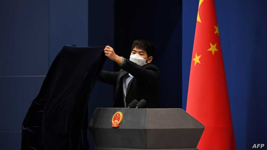 FILE - A worker wearing protective mask against the coronavirus covers the podium after the daily media briefing at the Foreign Ministry in Beijing, China, March 18, 2020.