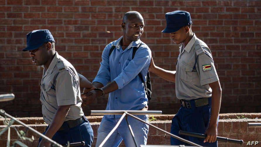 A man is arrested by police officers after resisting orders to vacate a vegetable market area in Bulawayo, Zimbabwe, March 31, 2020, on the second day of a lockdown to curb the spread of COVID-19.