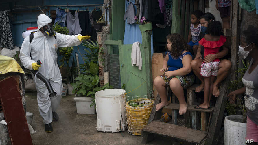 A worker gestures to residents as he sprays disinfectant in an alley to help contain the spread of the coronavirus, at the Santa Marta slum in Rio de Janeiro, Brazil, April 10, 2020.