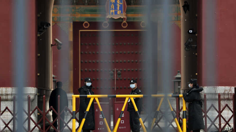Security guards wearing protective face masks stand guard at the closed gates of the Forbidden City, in Beijing, April 19, 2020.