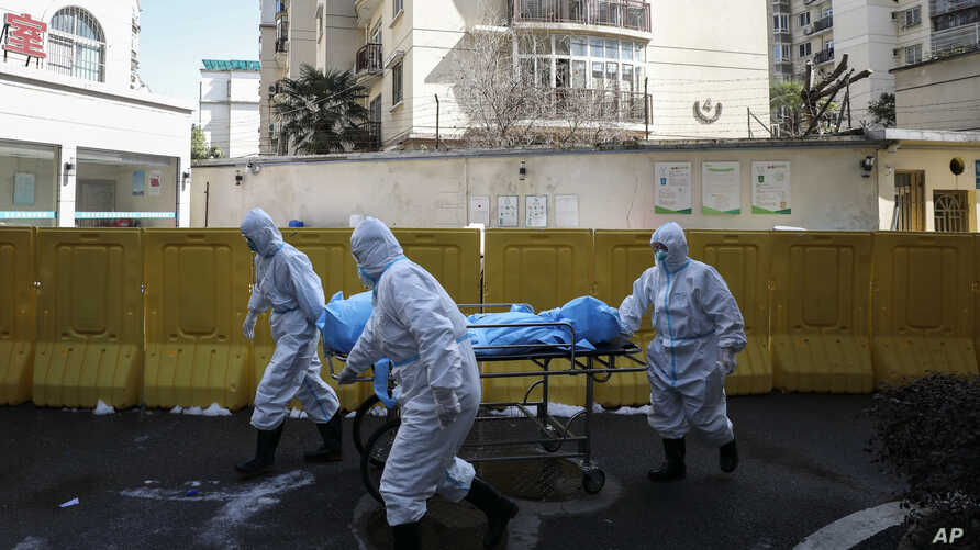 Medical workers move a person who died from COVID-19 at a hospital in Wuhan in central China's Hubei province, Feb. 16, 2020.