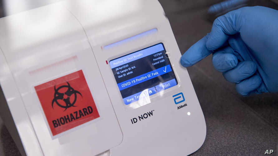 FILE - A scientist runs a mock COVID-19 sample test in Washington, D.C., April 28, 2020.