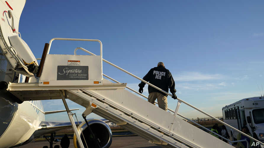 FILE - An Immigration and Customs Enforcement (ICE) officer awaits individuals to board a deporartion flight, in Houston, Texas, Nov. 16, 2018.