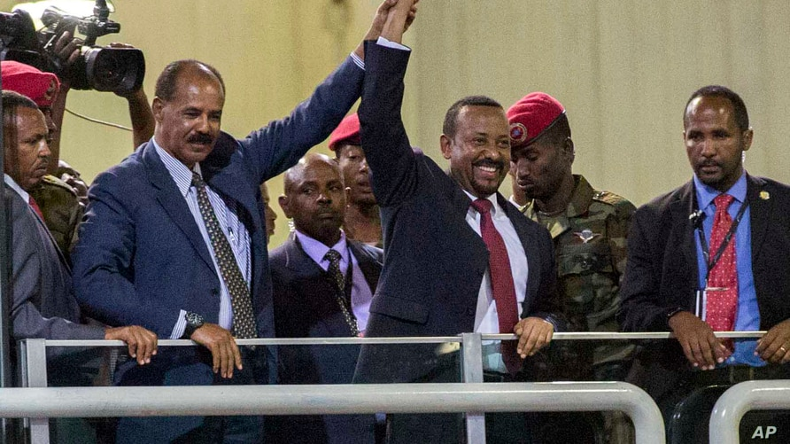 Eritrean President Isaias Afwerki, second left, and Ethiopia's Prime Minister Abiy Ahmed, center, hold hands as they wave at the crowds in Addis Ababa, Ethiopia, July 15, 2018.