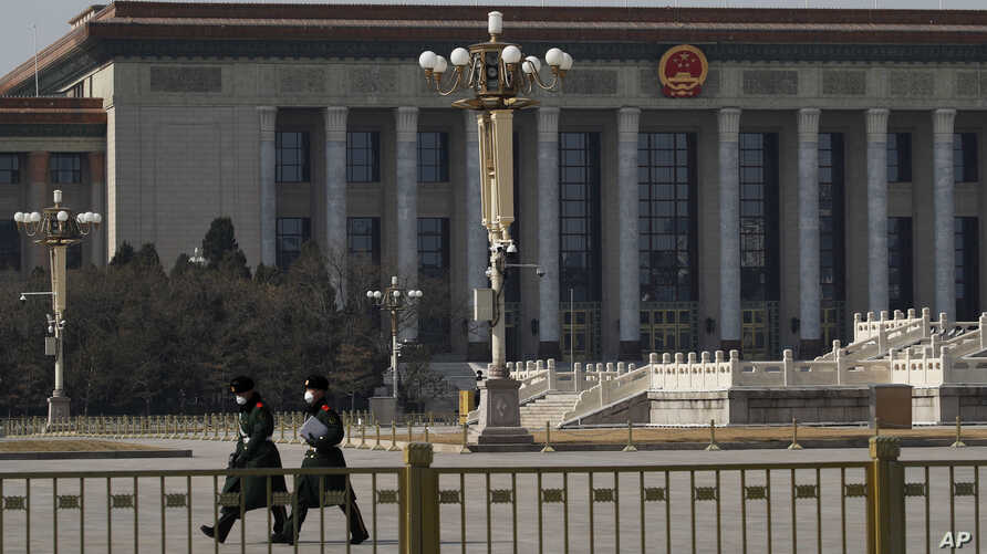 FILE - Paramilitary policemen wearing protective face masks walk in an empty Tiananmen Square against the backdrop of the Great Hall of the People in Beijing, China, Feb. 23, 2020.