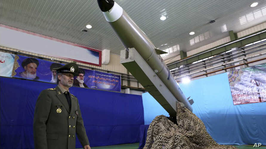 FILE - In this photo released by the official website of the Iranian Defense Ministry Aug. 13, 2018, Defense Minister Gen. Amir Hatami walks past a missile display at an undisclosed location in Iran.