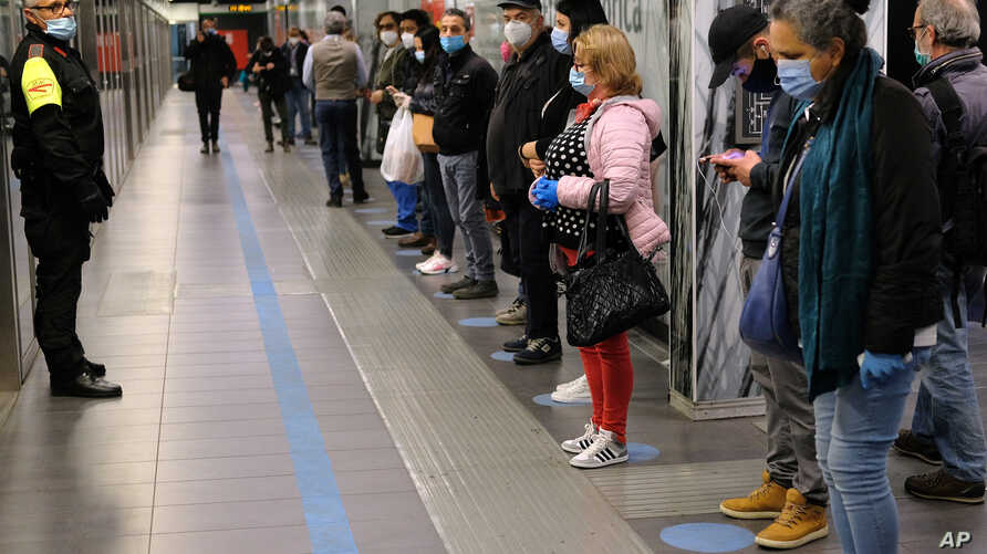 People stand apart from each other as they wait for a subway train in Rome, Italy, April 27, 2020.
