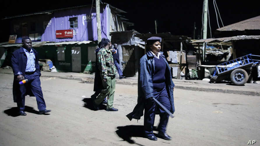 Kenyan police carrying batons and teargas patrol looking for people out after curfew in the Kibera slum in Nairobi, Kenya, March 29, 2020.