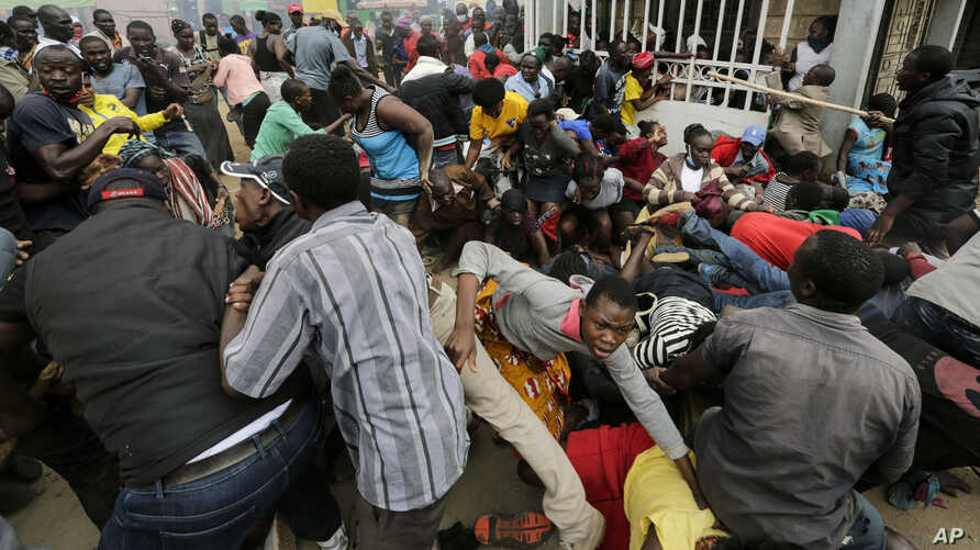 Residents desperate for a planned distribution of food for those suffering under Kenya's coronavirus-related restrictions push through a gate, creating a stampede, in Nairobi, Kenya, April 10, 2020.