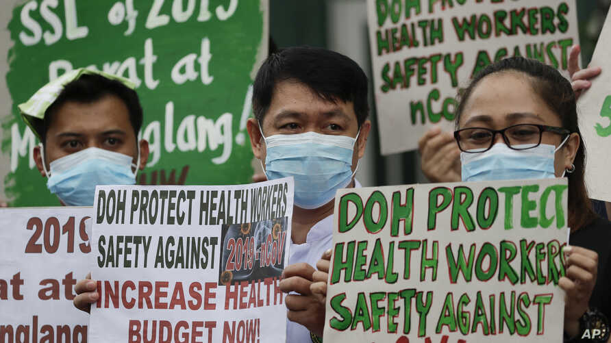 FILE - Health workers wearing protective masks hold signs during a rally outside a hospital in metropolitan Manila, Philippines, Feb. 7, 2020, demanding the government ensure their safety and raise their pay amid to the coronavirus threat.
