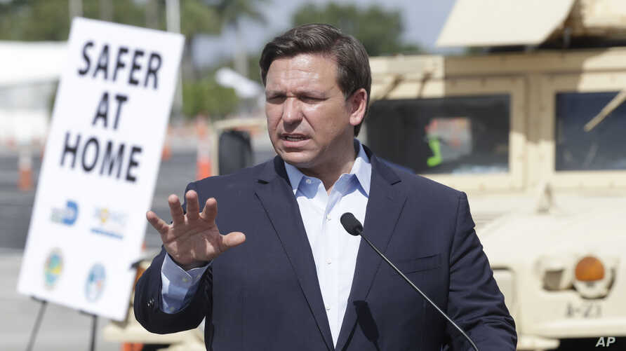 FILE - Florida Governor Ron DeSantis speaks during a news conference at a drive-through coronavirus testing site in front of Hard Rock Stadium, in Miami Gardens, Florida, March 30, 2020.