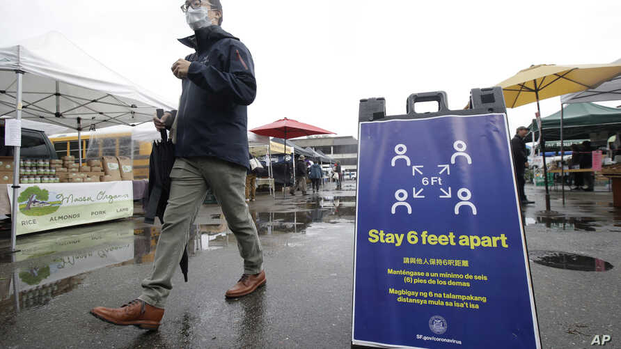 FILE - A man walks past a sign advising social distancing, at the Ferry Plaza Farmers Market, in San Francisco, California, March 28, 2020.