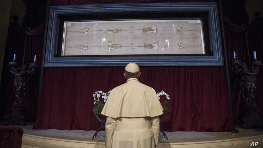 FILE - Pope Francis prays in front of the Holy Shroud of Turin, the 14 foot-long linen revered by Christians as the burial cloth of Jesus, on display at the Cathedral of Turin, Italy, June 21, 2015.