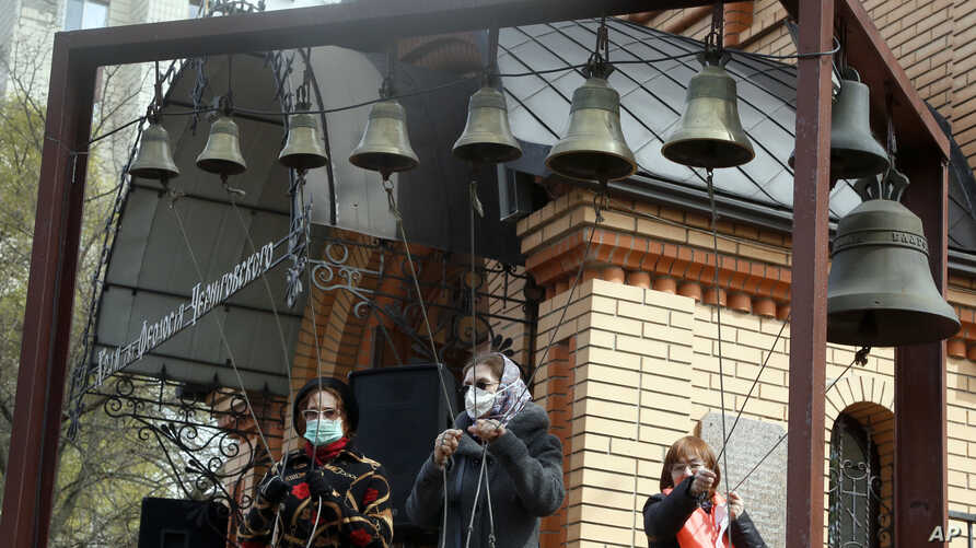 Women wearing face masks to protect against coronavirus ring the church bells at a memorial of the Chernobyl tragedy victims in capital Kyiv, Ukraine, April 26, 2020.
