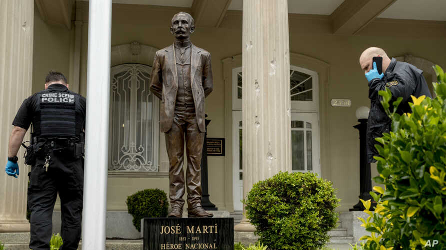 Bullet holes are visible on a column behind a statue of Cuban independence hero José Martí as Secret Service officers investigate after police say a person with an assault rifle opened fire at the Cuban Embassy, April 30, 2020, in Washington.