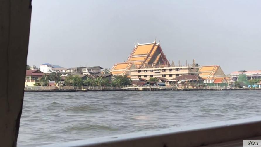 A boat rides past a temple in Bangkok. Thailand is one of the nations with low COVID-19 cases, likely due to low testing. (VOA News)