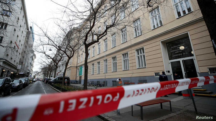 FILE - Policemen guard the entrance of a school after authorities put it under isolation because of suspicions of a coronavirus case, in Vienna, Austria Feb. 26, 2020. Austria shut all of its schools early in the coronavirus outbreak.